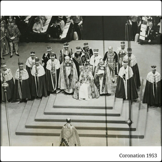 Photograph showing HM Queen Elizabeth II seated, wearing the Imperial State Crown, and carrying the Sceptre with the Dove and Sceptre with the Cross, accompanied by the Archbishops. peers, and Knights of the Garter.
