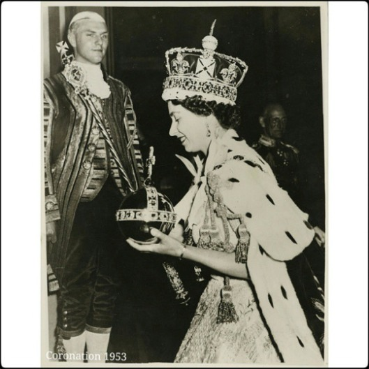 Photograph of The Queen, newly crowned, as she steps from the State Coach on her return to Buckingham Palace from Westminster Abbey. She holds the Orb in her left hand, the Sceptre with the Cross in her right hand; she wears Imperial State Crown. A Footman stands in background. .