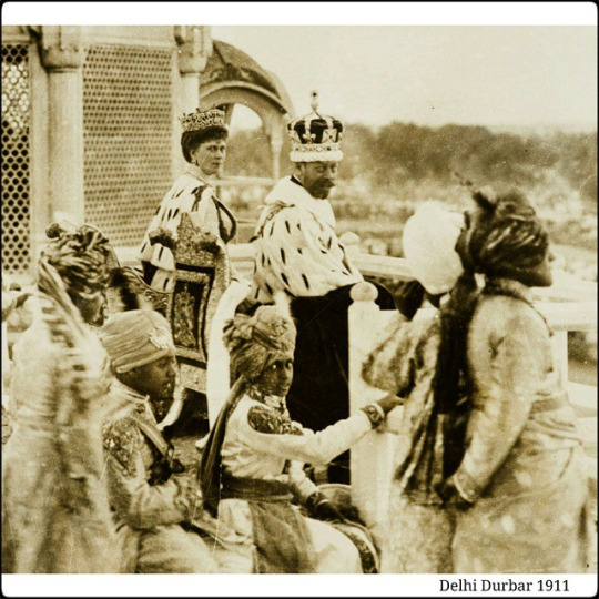 Photograph of King George V wearing Coronation robes and the Imperial Crown of India turns, smiling, to face the viewer. On his left is seated Queen Mary who also turns to face the viewer. She wears the Durbar diadem and State robes. In the foreground are seated Indian boys and men dressed in traditional Indian costume. Photographed in the Red Fort, Coronation Park.