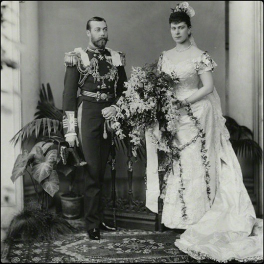 Photograph of the Duke and Duchess of York, later King George V and Queen Mary: full length portrait, Princess Mary seated in her wedding gown of ivory silk satin, trimmed with Honiton lace and orange blossom. The Duke in full military uniform decorated with many orders.